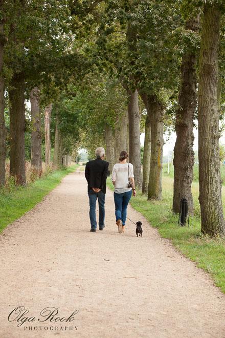 Nostalgische foto van een vader en zijn volwassene dochter lopend door een groene laan in een park.