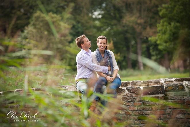 Romantische kleurenfoto van een stel: ze zitten op een stenen brug in een park.