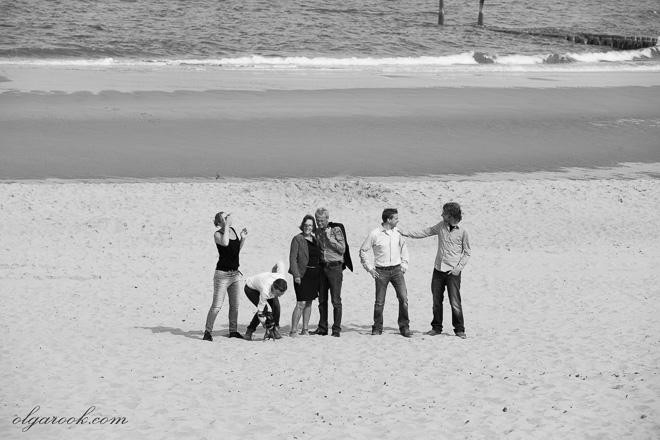 Foto van een familie op het strand. Ze zijn vrolijk en relaxed.