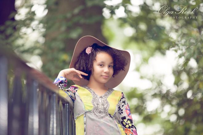 Romantisch en schilderachtig kinderportret: een krullerig meisje met een hoedje