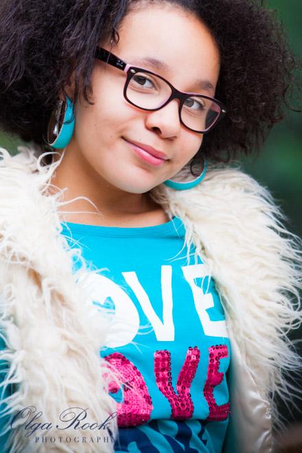 Portret van een krullerig meisje met een brilletje en oorbellen.