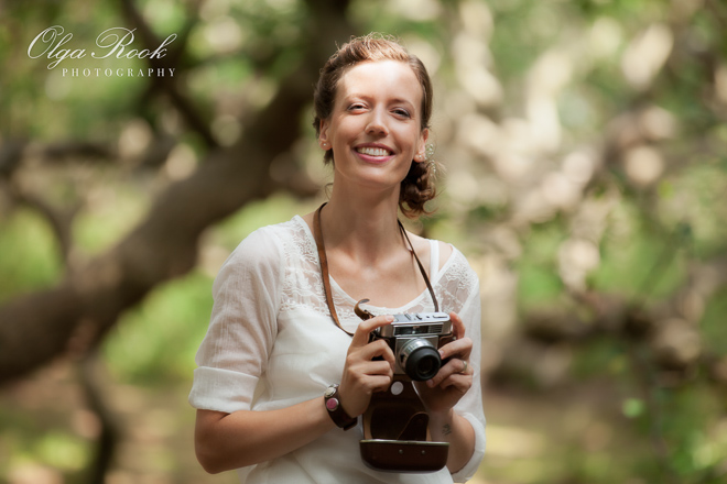 Natural and romantic portrait of a girl with an antique camera in a forest.