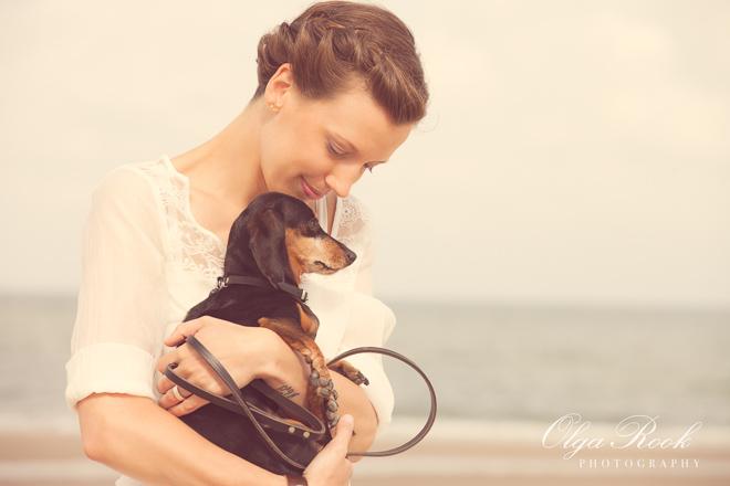 Foto van een mooie vrouw met een teckel op een strand: warme pastelkleuren maken het extra dromerig en romantisch.