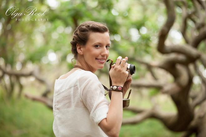 Romantische portret van een jonge vrouw met een vintage camera in een bos.
