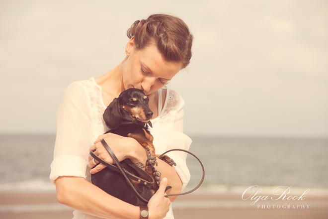 Dromerige portret van een meisje met een hondje bij de zee: ze houdt haar hondje in haar handen en geeft hem een zoen.