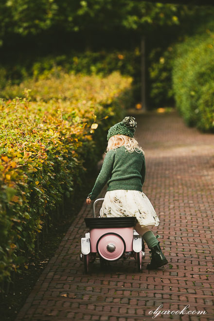 Autumn colors and timeless nostalgic atmosphere in a portrait of a little girl with her pedal car in a park