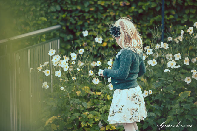 Photo of a little girl plucking flowers in a garden