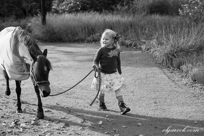 Black and white photo of a small girl leading a pony through a park