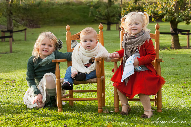 Colorful portrait of three little children on small wooden chairs in a garden
