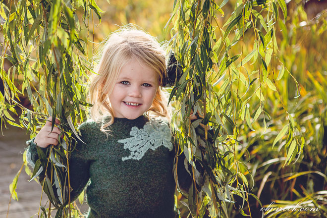 Portrait of a small blond girl laughing as she holds the branches of a willow making a frame around her face. The photo has rich autumn tones.