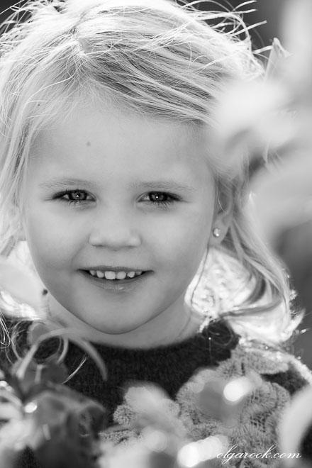 Zwart-wit portret van een klein blond meisje in een tuin