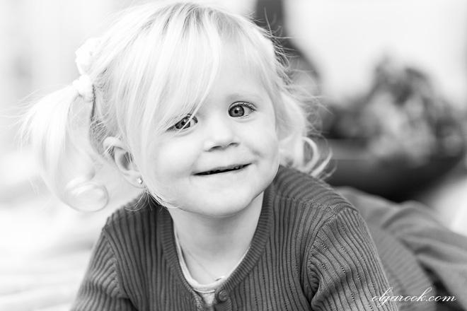 Zwart-witte portret van een klein lachend blond meisje