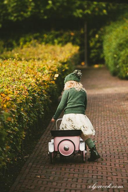 Kinderportret met rijke herfstkleuren: klein meisje met een trapauto in een park