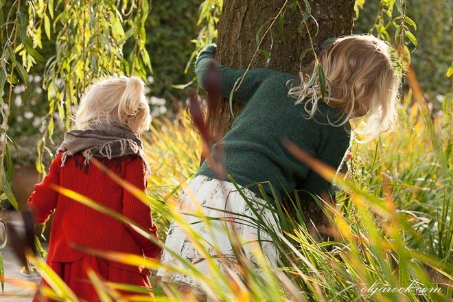 Foto van twee kleine meisjes spelend naast een wilg