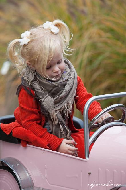 Foto van een klein blond meisje in een trapauto
