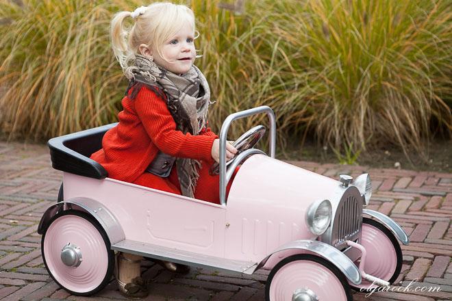 Foto van een klein lachend meisje in een roze trapauto.