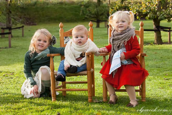 Vrolijke kleurenfoto van drie kleine kinderen in een tuin