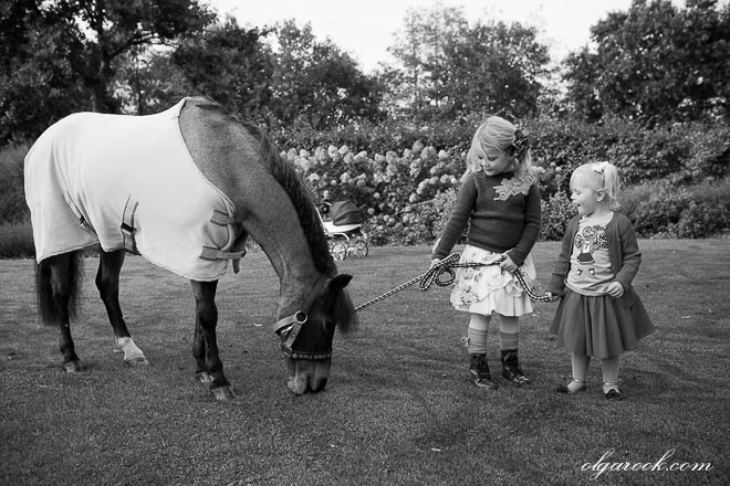 Zwart-witte foto van kleine meisjes die met een pony in een park wandelen.