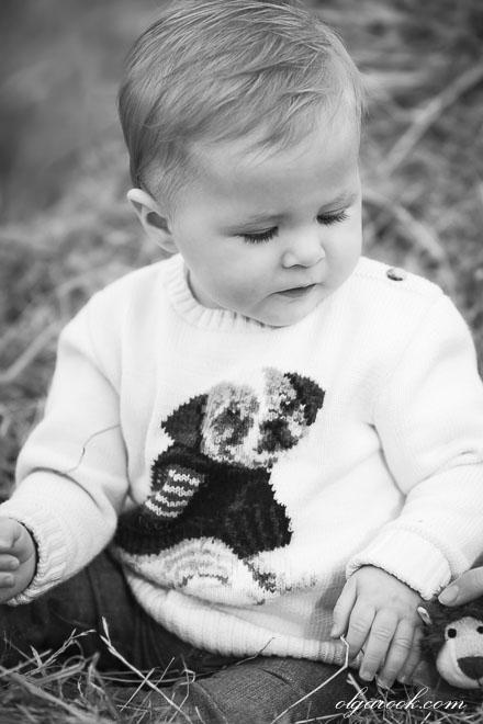 Foto van een klein jongetje, die in het hooi speelt