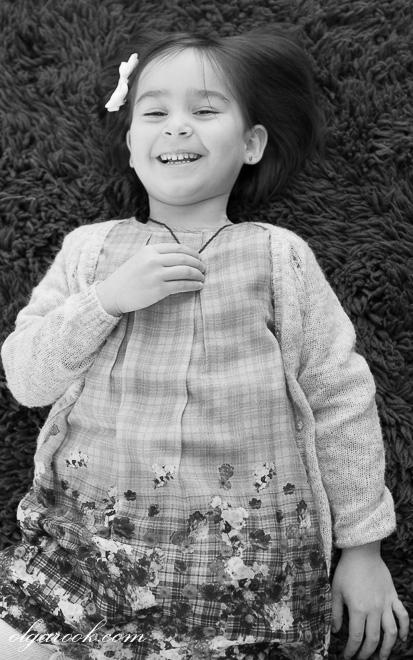 Foto van een klein meisje die op de vloer ligt te lachen