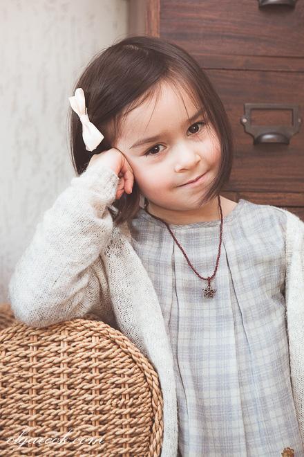 Klassieke portret van een klein meisje die thuis in haar interieur poseert.