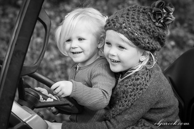 Black and white portrait of two little girls driving a tractor