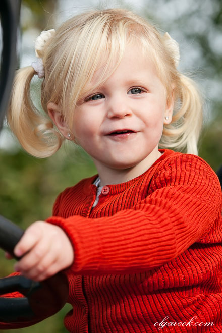 Color portrait of a small blond girl behind the steer of a tractor: she looks really happy.
