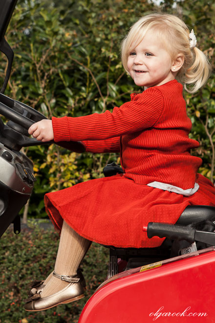 Photo of a little blond girl dressed in red and sitting behind the steer of a tractor