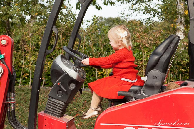 Little blond girl driving a tractor