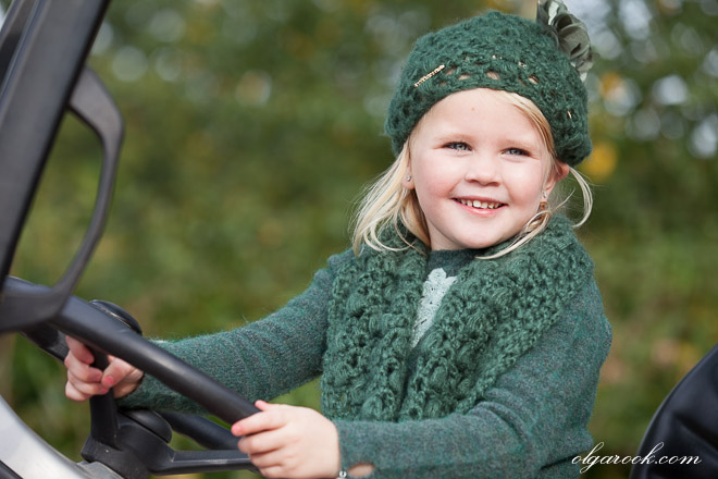Portrait of a small girl dressed in green and smiling happily as she holds a steer wheel of a tractor