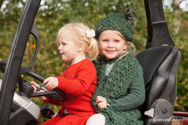 Twee kleine meisjes die een tractor rijden