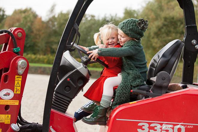 Foto van twee kleine meisjes op een tractor: ze proberen het samen te sturen.
