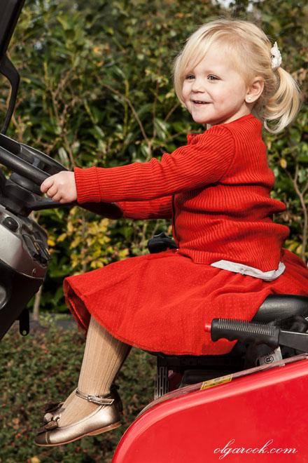 Foto van een klein blond meisje achter het stuur op een tractor