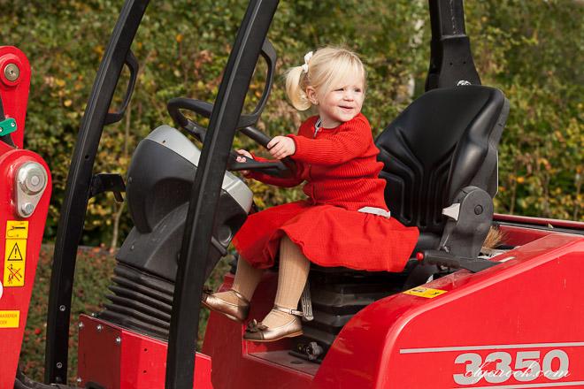 Klein meisje in rood achter het stuur op een tractor