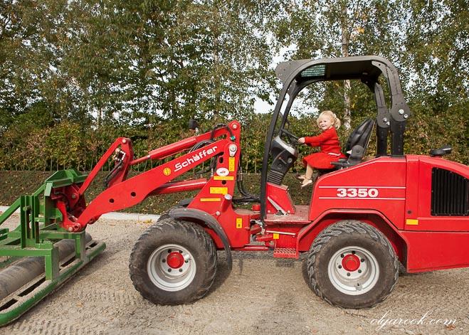 Foto van een rode tractor met een klein meisje achter het stuur