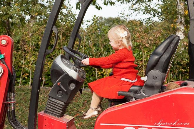 Foto van een klein meisje op een tractor achter het stuur