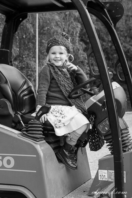 Zwart-wit portret van een klein meisje poserend achter het stuur op een tractor