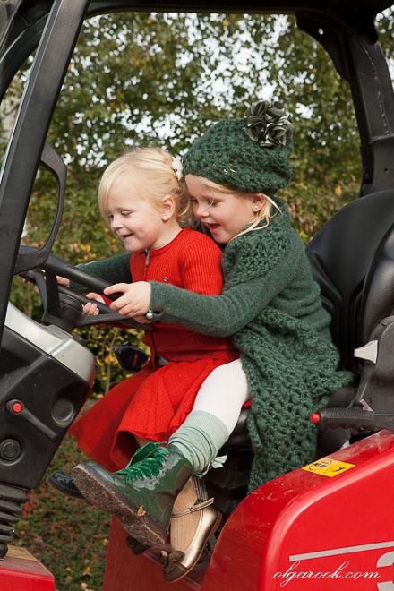 Foto van twee kleine vrolijke meisjes die een tractor rijden