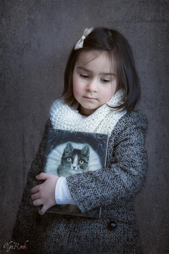 Melancholic portrait of a little brunette girl with a painting of a cat wearing a collar.