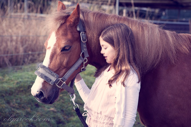 Dreamy vintage style portrait of a little girl with a pony