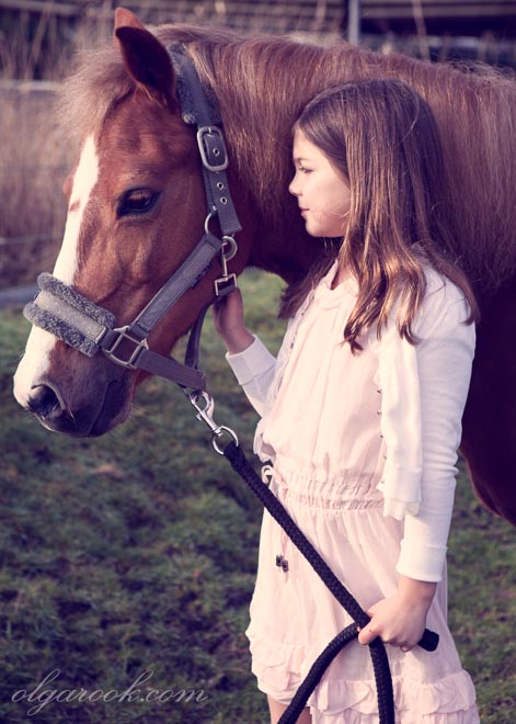 Color portrait of a little girl standing next to her horse