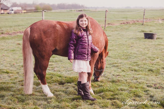 Photo of a little girl and a pony in a field.