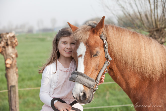 Dreamy photo of a little girl embracing a horse. The photo is made near the riding school in Delft and the scene behind is a typical Dutch landscape on a beautiful spring morning.