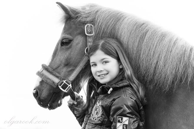 Zwart-wit portret van een klein meisje met een paard