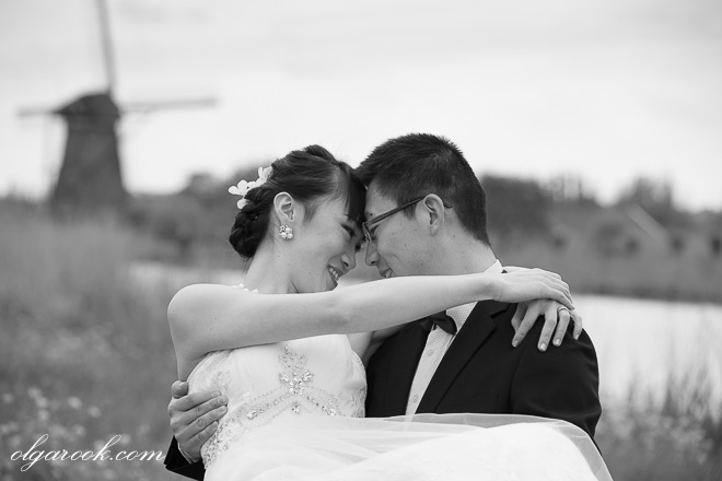 Nostalgic black and white portrait of an Asian couple with a Dutch windmill in the background.