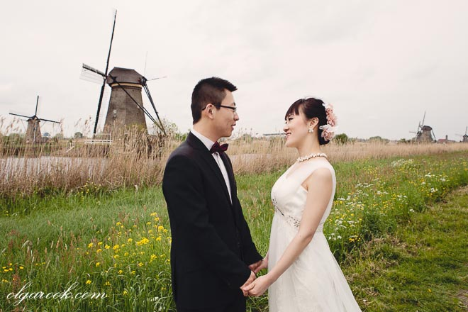 Loveshoot of a Chinese couple with the windmills of Kinderdijk in Holland.