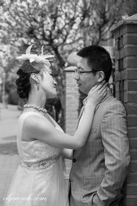 Retro-like portrait of an Asian couple on a street: the bride touches the groom's face in a graceful and seductive manner.