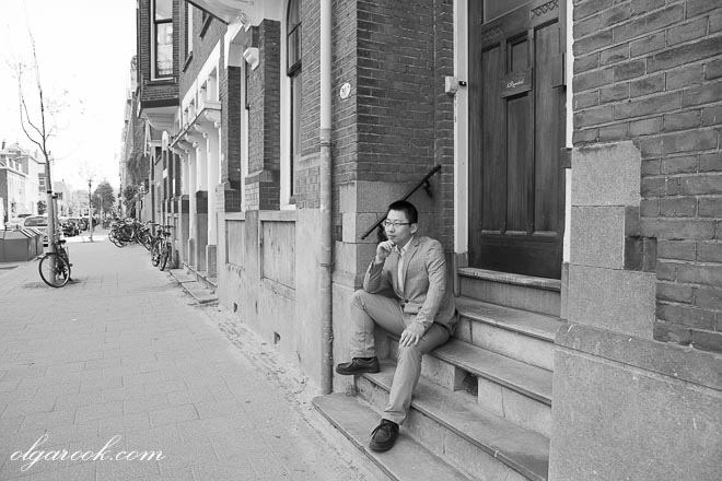 Portrait of a young Asian man sitting on the stairs in front of a house on an old street in Rotterdam.