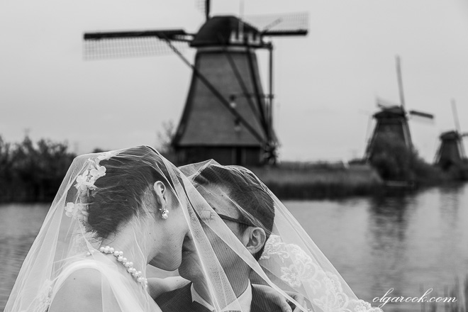 Classic and nostalgic portrait of a couple at the windmills of Kinderdijk in Holland.