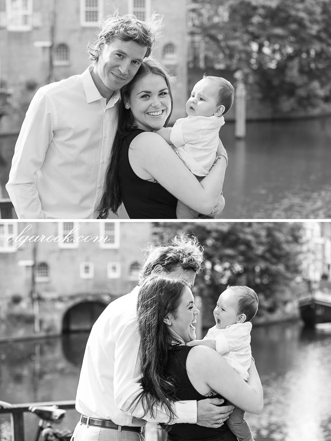 Black and white portrait of a young couple with a baby standing next to a canal in Rotterdam